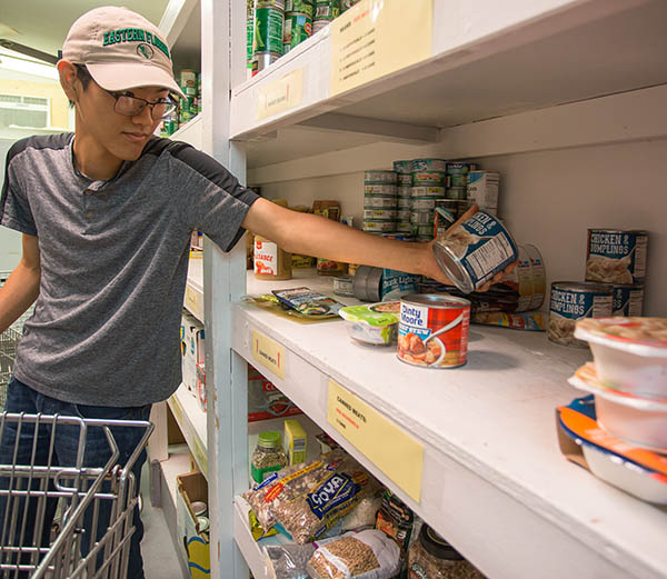 student stocking food pantry shelf