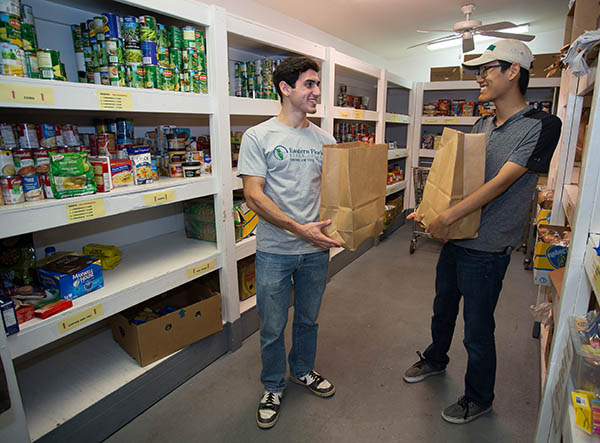 two students with grocery bags in food pantry